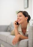 Mujer que pone en el sofá y el teléfono celular de discurso Foto de archivo libre de regalías