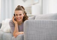 Mujer que pone en el sofá y el teléfono celular que habla Imágenes de archivo libres de regalías