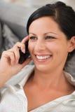 Mujer que pone en el sofá y el teléfono móvil de discurso Imágenes de archivo libres de regalías