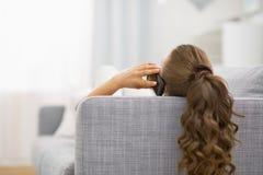 Mujer que pone en el sofá y el teléfono móvil que habla Fotos de archivo