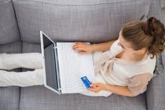 Mujer que pone en el sofá con el ordenador portátil y la tarjeta de crédito Fotos de archivo libres de regalías