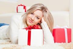 Mujer que pone en el suelo con los regalos Foto de archivo libre de regalías
