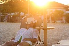 Mujer que pone en el Sunbed y que duerme en la playa Imágenes de archivo libres de regalías