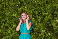 Mujer que pone en hierba con los auriculares Fotografía de archivo
