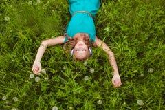 Mujer que pone en hierba con los auriculares Fotografía de archivo libre de regalías