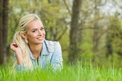 Mujer que pone en hierba verde Fotos de archivo