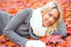 Mujer que pone en hojas rojas y la sonrisa Fotografía de archivo libre de regalías