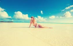 Mujer que pone en la arena del amarillo de la playa con el fondo tropical del océano del cielo azul Fotografía de archivo