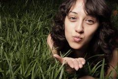 Mujer que pone en la hierba Imagenes de archivo