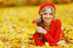 Mujer que pone en las hojas de otoño Foto de archivo libre de regalías