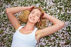 Mujer que pone en los flores de cereza Imagenes de archivo