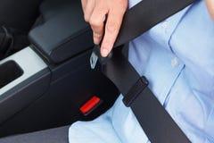 Mujer que pone en su cinturón de seguridad Fotografía de archivo
