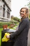 Mujer que pone la basura del plástico en compartimiento de basura Fotos de archivo libres de regalías