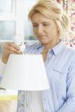 Mujer que pone la bombilla de la energía baja en la lámpara en casa Foto de archivo libre de regalías