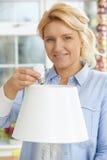 Mujer que pone la bombilla de la energía baja LED en la lámpara en casa Imagenes de archivo