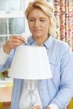 Mujer que pone la bombilla de la energía baja LED en la lámpara en casa Fotos de archivo libres de regalías