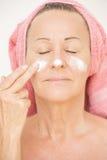 Mujer que pone la crema en cara Fotografía de archivo libre de regalías