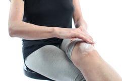 Mujer que pone la crema en su rodilla Imágenes de archivo libres de regalías
