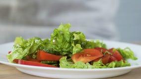 Mujer que pone la ensalada de las verduras frescas del cuenco a la placa, aperitivo sano, detox almacen de video