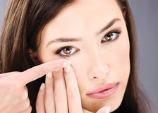 Mujer que pone la lente de contacto en su ojo Imagen de archivo libre de regalías