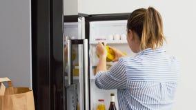 Mujer que pone la nueva comida comprada para dirigirse el refrigerador almacen de metraje de vídeo