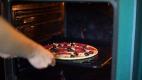 Mujer que pone la pizza en el horno almacen de video