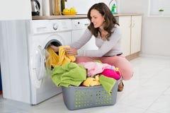 Mujer que pone la ropa en la lavadora Imágenes de archivo libres de regalías