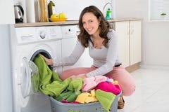 Mujer que pone la ropa en la lavadora Fotos de archivo