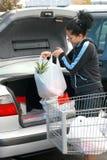 Mujer que pone las tiendas de comestibles en tronco Fotos de archivo libres de regalías