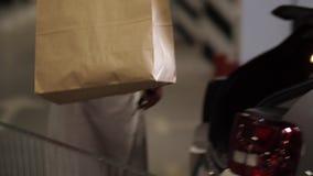 Mujer que pone los paquetes con las compras en tronco de coche almacen de metraje de vídeo