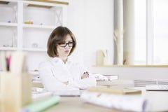 Mujer que pone mala cara en el escritorio de oficina Imagen de archivo