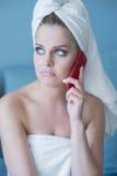 Mujer que pone mala cara en toalla de baño con el teléfono celular rojo Fotografía de archivo
