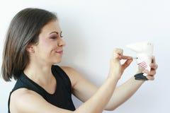 Mujer que pone monedas en su moneybox Imagenes de archivo