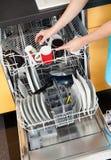 Mujer que pone platos en el lavaplatos Fotos de archivo
