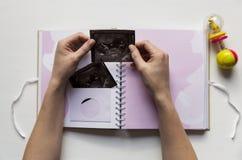 Mujer que pone sonogram del ` s del bebé en libro de la memoria del año del ` s del bebé el primer Fotos de archivo libres de regalías