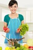 Mujer que pone un manojo de ingredientes sanos Imágenes de archivo libres de regalías