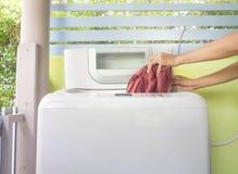 Mujer que pone un paño en la lavadora fotos de archivo