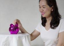Mujer que pone una moneda en la caja de dinero Imágenes de archivo libres de regalías