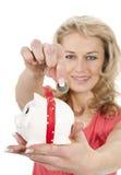 Mujer que pone una moneda euro en piggybank Fotografía de archivo libre de regalías
