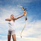 Mujer que practica con el arco y la flecha Imagen de archivo