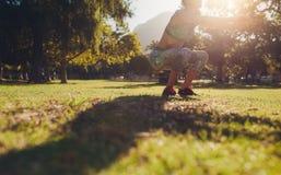 Mujer que practica ejercicio agazapado en el parque Foto de archivo libre de regalías