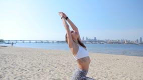 Mujer que practica realizando uotdoors de la yoga-asanas en la playa de la arena situación atlética delgada joven de la mujer en  almacen de video