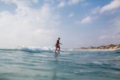 Mujer que practica surf con el tablero que practica surf Fotografía de archivo