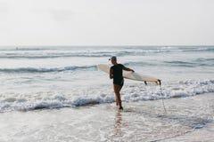 Mujer que practica surf con la opinión trasera del tablero que practica surf Imágenes de archivo libres de regalías