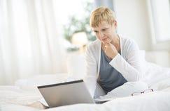 Mujer que practica surf en el ordenador portátil en dormitorio Imágenes de archivo libres de regalías