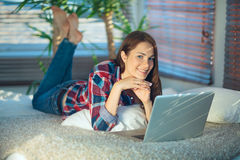 Mujer que practica surf la red en casa Imágenes de archivo libres de regalías