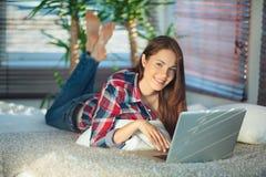 Mujer que practica surf la red en casa Imagen de archivo