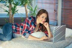 Mujer que practica surf la red en el sofá Imágenes de archivo libres de regalías