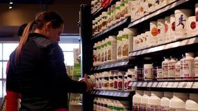 Mujer que pregunta a trabajador acerca de la pregunta de la comida sana