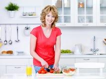 Mujer que prepara el alimento en la cocina Foto de archivo
